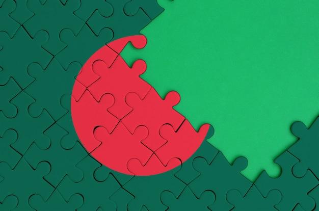 방글라데시 깃발은 오른쪽에 무료 녹색 복사 공간이있는 완성 된 직소 퍼즐에 그려져 있습니다.