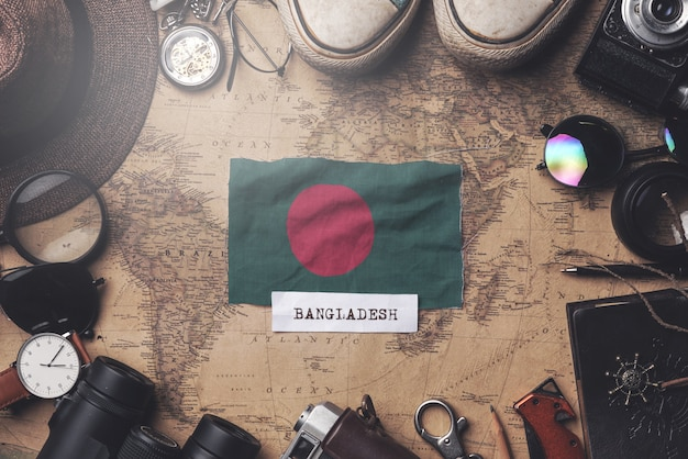 Bangladesh flag between traveler's accessories on old vintage map. overhead shot