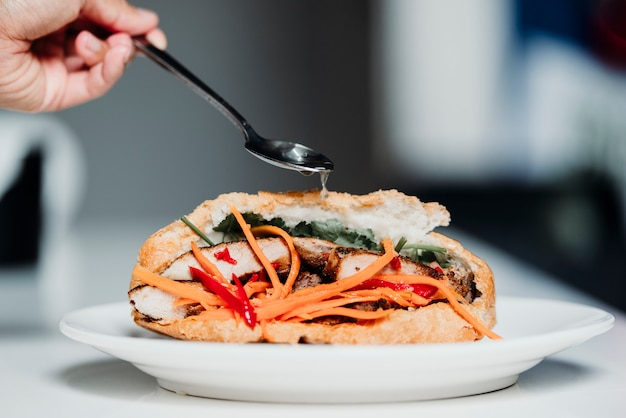 Banh mi is the traditional vietnamese sandwich with pickled carrot, lettuce, fish sauce and and meat