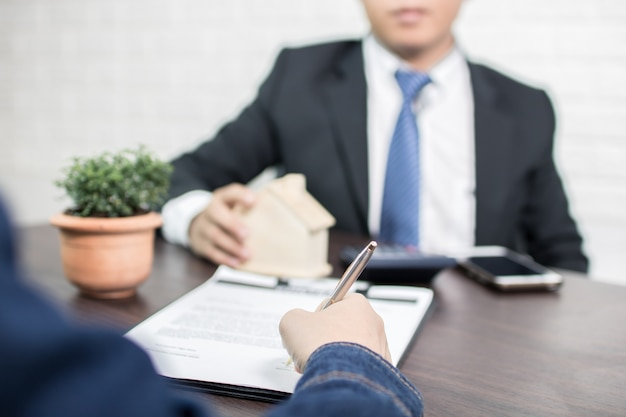 Bank agency explaining to home loan people and buyer signing contract