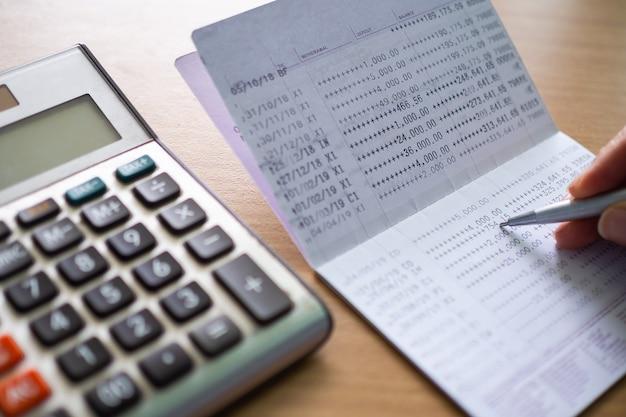 나무 테이블에 펜과 계산기와 은행 책. 비즈니스 및 금융 계획 돈 절약, 주식 시장 개념.