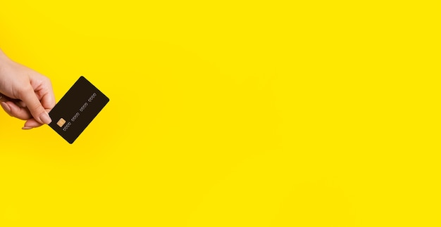 黄色の背景、テキスト用のスペースのあるパノラマモックアップの上に銀行カードを手に
