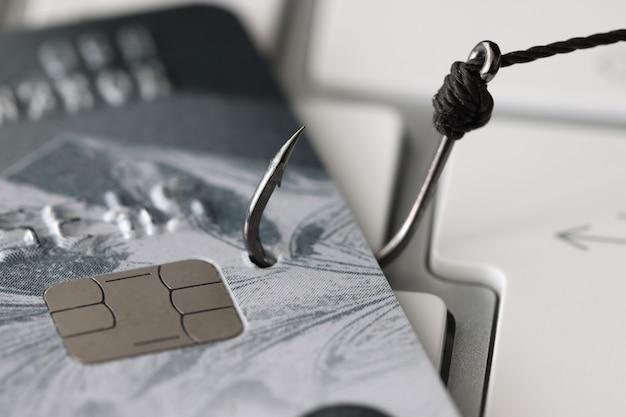 Банковская карта привязана к крючку, лежащему на компьютерной клавиатуре крупным планом, концепция интернет-мошенничества
