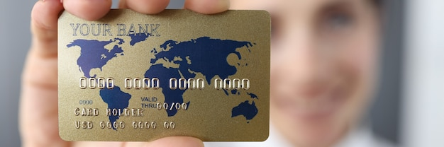 Банковская кредитная карта на фоне улыбающейся женщины.