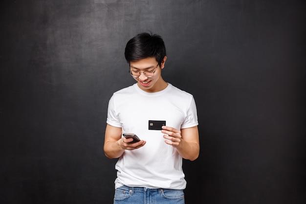 銀行、金融、支払いの概念。 tシャツの若いアジアの男、ショッピングアプリケーションでの請求情報の挿入としてクレジットカードを保持、携帯電話のディスプレイを見て笑顔、新しい服をインターネットで購入