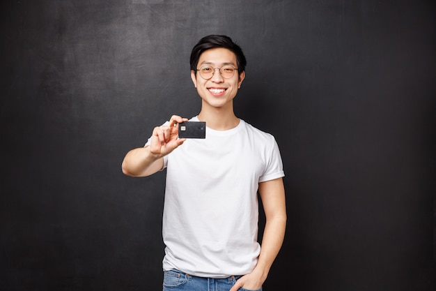 Bank, finance and payment concept. portrait of friendly confident young asian male showing credit card at camera with pleased beaming smile, advice open account at put money,