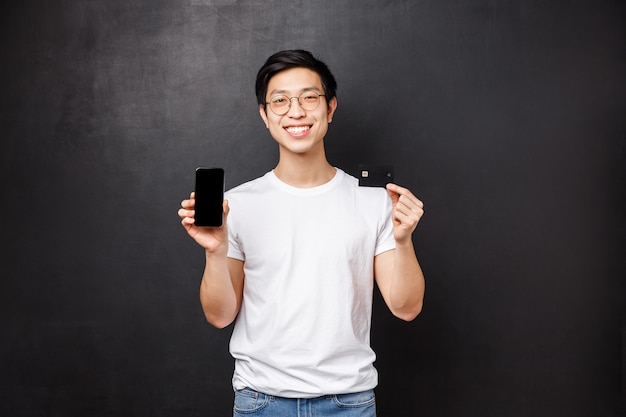Bank, finance and payment concept. portrait of simple asian guy in white t-shirt introducing new application for banking users, holding credit card and mobile phone, smiling on black wall
