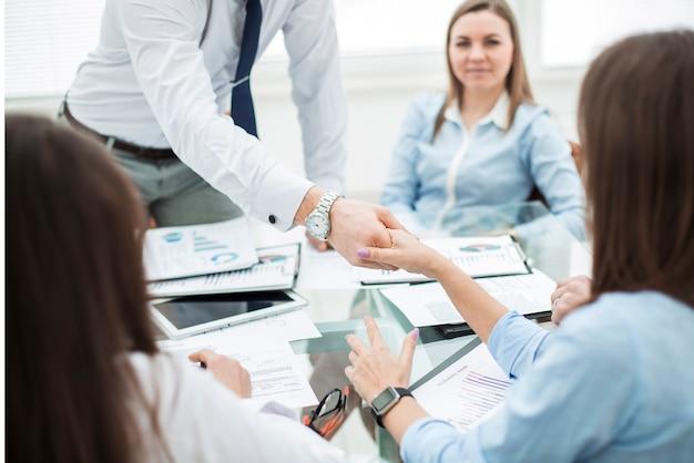 Менеджер банка и клиент пожимают друг другу руки после подписания выгодного контракта на фоне современного офиса.