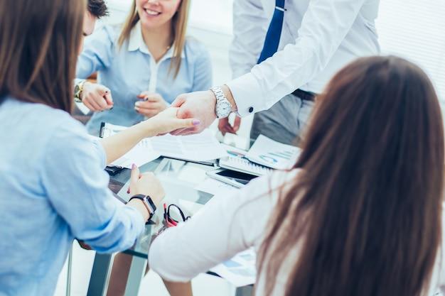 銀行のマネージャーと顧客は、近代的なオフィスの背景で有利な契約に署名した後、握手します