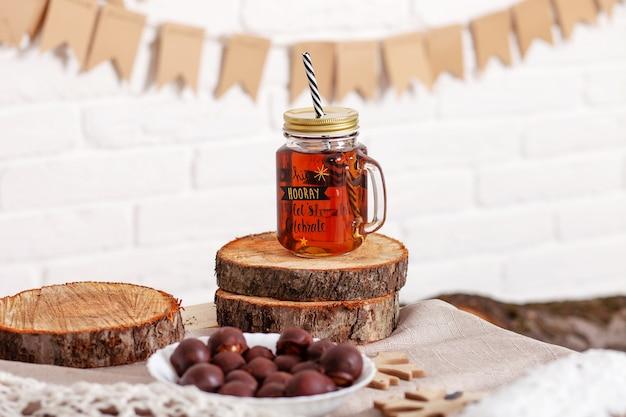 冷たいお茶でマグカップをバンクします。秋と冬の時間。飲み物とお茶の瓶