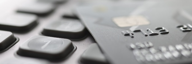Bank plastic card lying on calculator closeup payment of taxes concept