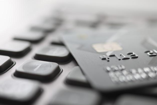 Банковская пластиковая карта, лежащая на крупном плане калькулятора. концепция оплаты налогов