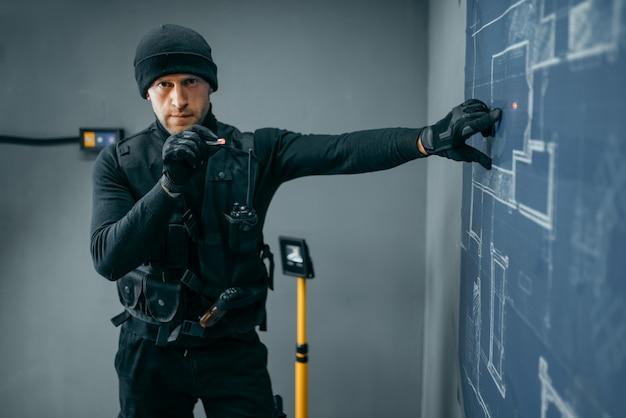 Ограбление банка, мужчина-грабитель в черной форме