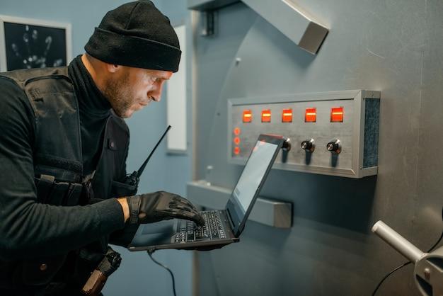 Ограбление банка, мужчина-грабитель с ноутбуком пытается открыть дверь хранилища. преступная профессия, понятие кражи