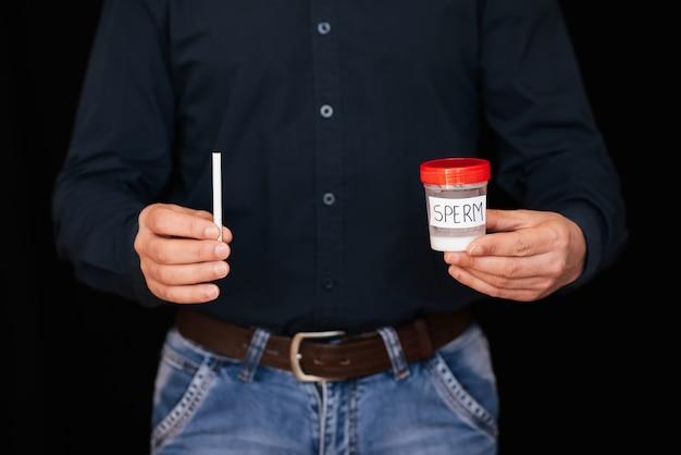 銀行の精液と男性の手の中のタバコ