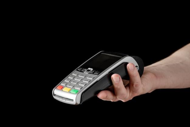Банковский терминал для оплаты кредитными картами в руке на черном фоне