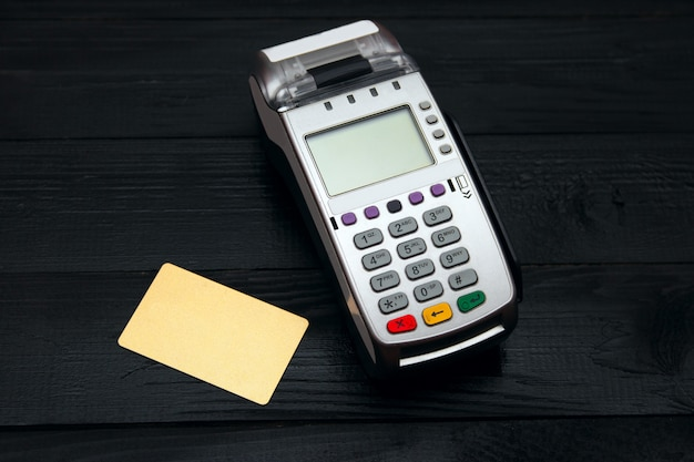 Bank terminal and payment card on black background