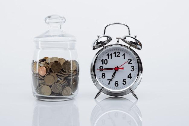동전과 알람 시계와 함께 은행. 저축 및 돈 개념.