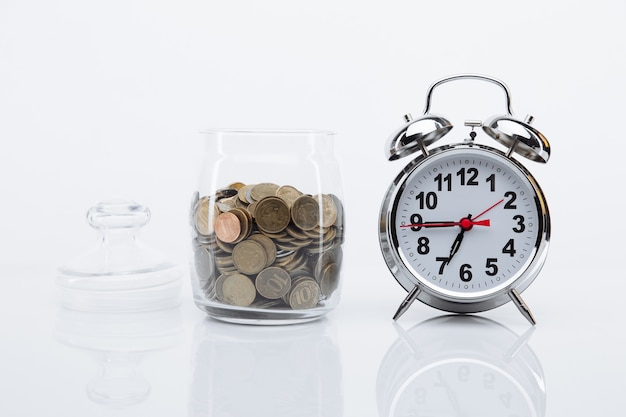 コインと目覚まし時計のある銀行。時間はお金の概念です。