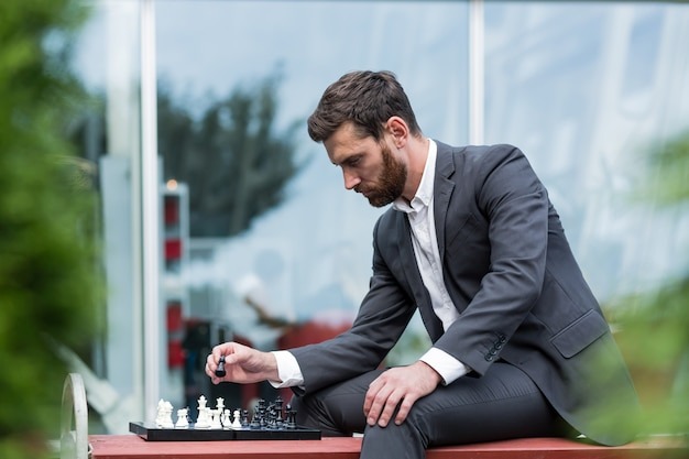 Banker male businessman playing chess sitting on bench near office, pensive making strategic move