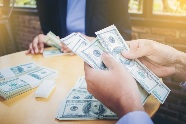 Banker's hands counting dollar banknotes on the table