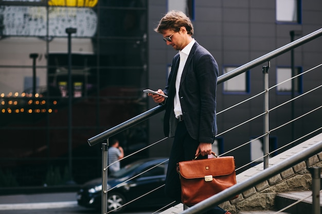 A banker in a stylish suit with a cell phone is going down the stairs
