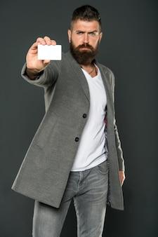 은행 및 신용 개념입니다. 플라스틱 은행 카드. 쉬운 돈 신용. 어떤 은행 카드를 쉽게 얻을 수 있습니다. 간편한 쇼핑. 신용 카드는 당신에게 자유와 자신감을 줍니다. 남자 수염된 힙스터는 플라스틱 빈 카드를 들고 있습니다.