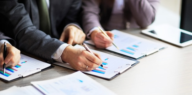 Banking business or financial analyst desktop accounting charts pens indicates in the graphics