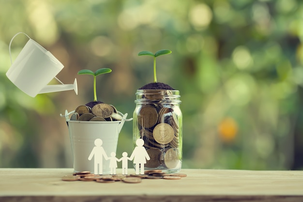 Banking and finance, saving money concept: water being poured on green sprout with glass bottle and bucket full of coins with family members. depicts investing money for earning growth.