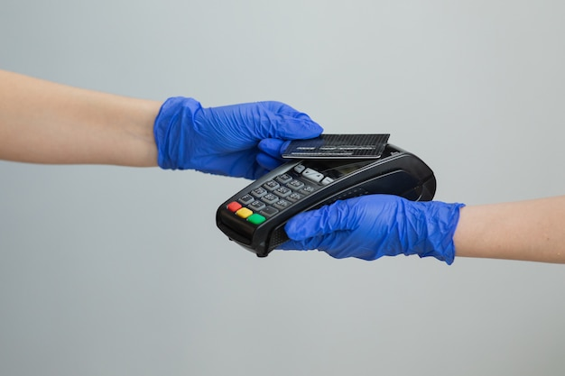 電子マネーの銀行サービス。経済的な成功と安全。金銭取引用クレジットカード機。クレジットカードで手袋をはめた女性がpos端子をスワイプし、ピンコードを入力します。