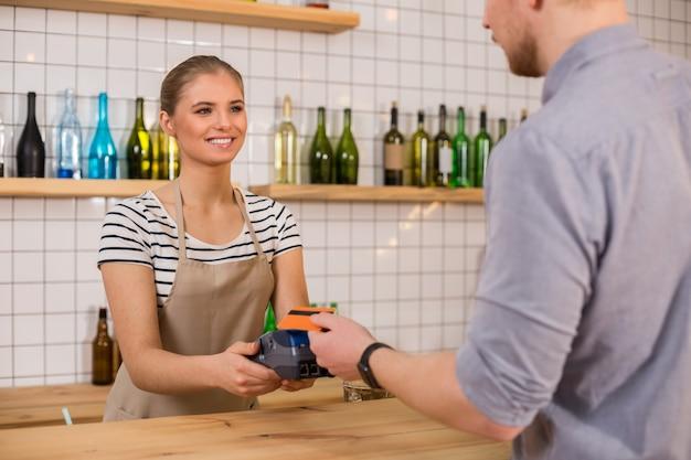 銀行システム。クレジットカード端末を持って、支払いをしながら顧客を見ているとても素敵な女性を喜ばせました