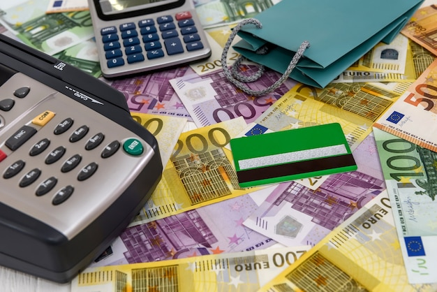 Banking terminal on euro banknotes background close up