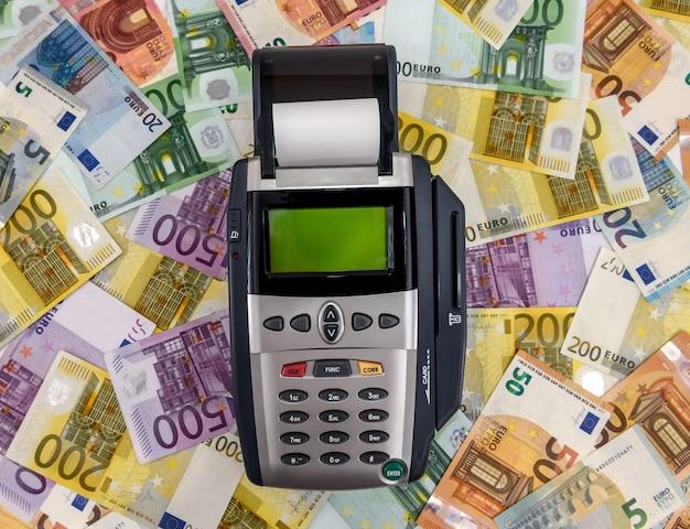 유로 지폐 배경에 은행 터미널을 닫습니다.