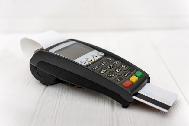Banking terminal with credit card on wooden background