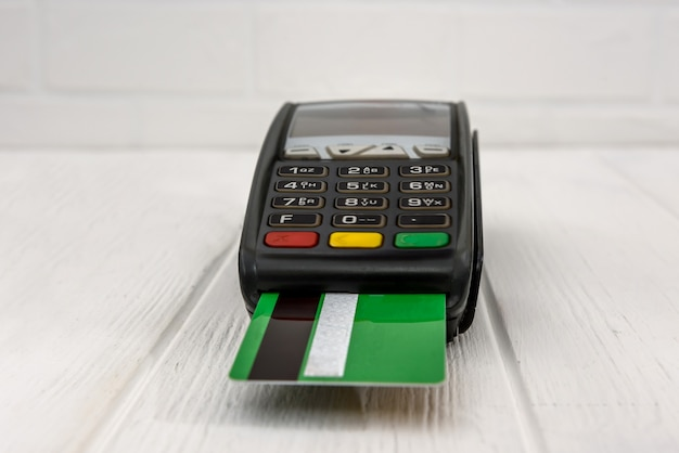 Banking terminal with credit card on wooden table
