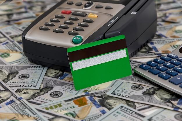 Банковский терминал с зеленой кредитной картой и долларовым фоном