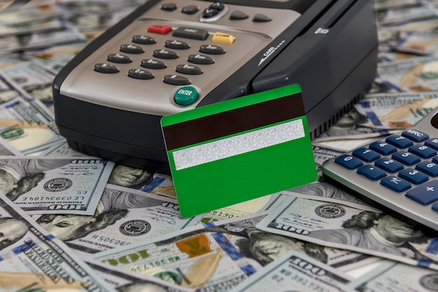 Banking terminal with green credit card and dollar background