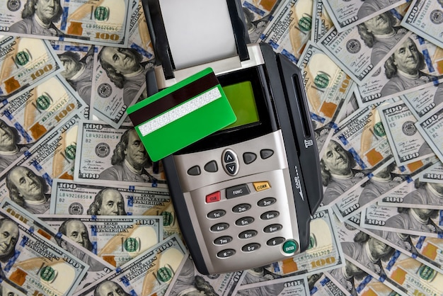 Banking terminal with green credit card and dollar surface