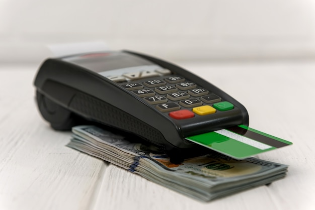 Banking terminal with green credit card and dollar