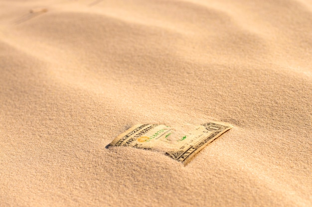 Banknote covered with sand