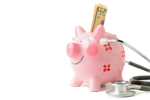Banknote in piggy bank and stethoscope  isolated