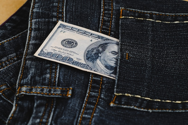 Banknote split out of a jean pocket .
