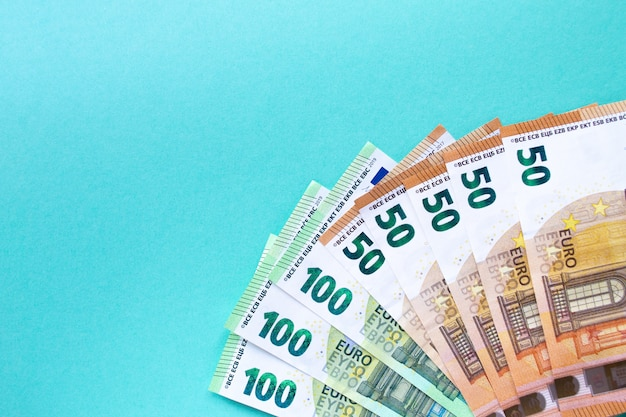 Banknotes of 100 and 50 euros laid out on a blue background
