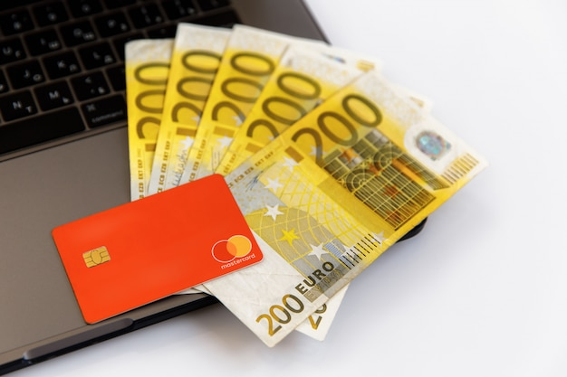 Banknotes of 200 euros lie near the laptop and credit card