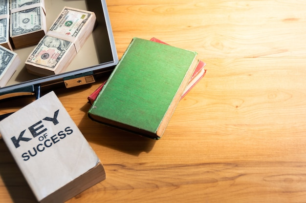 Banknotes in briefcase, old book and quide to success on wooden table.