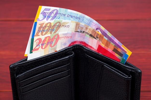 Banknotes from israel in a black wallet
