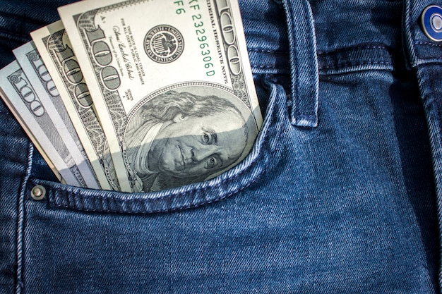 Banknotes of hundreds of us dollars sticking out of a pocket of jeans