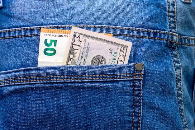 ブルージーンズのバックポケットのクローズアップで50ユーロとドルの紙幣。