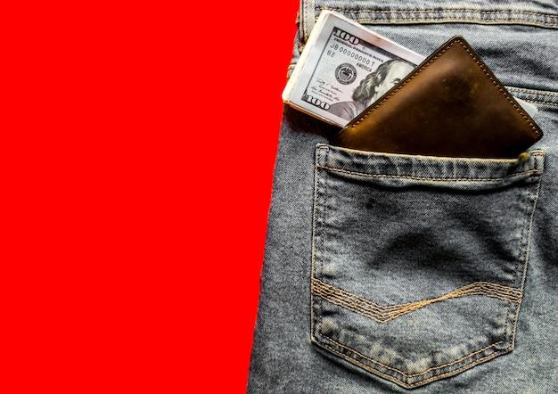 Банкноты в кармане джинсов, в кошельке. понятие о достатке и заработной плате. кошелек и доллары в кармане джинсов. скопируйте пространство, место для текста, плоскую планировку. синие джинсы на красном фоне.