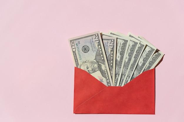 ピンクの背景に赤い封筒に100ドルの紙幣。碑文の節約とドル札の封筒。あなたの財政を管理し、お金の概念を節約します。コピースペース